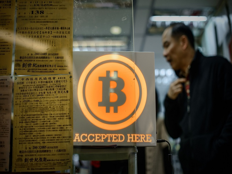 A man walks out of a shop displaying a bitcoin sign during the opening ceremony of the first bitcoin retail shop in Hong Kong on February 28, 2014. Bitcoin was invented in the wake of the global financial crisis by a mysterious computer guru using the pseudonym Satoshi Nakamoto and unlike other currencies, it does not have the backing of a central bank or government. AFP PHOTO / Philippe LopezPHILIPPE LOPEZ/AFP/Getty Images