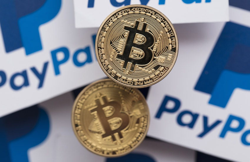Two bitcoins on top of papers with PayPal symbol on them, representing payment methods using blockchain