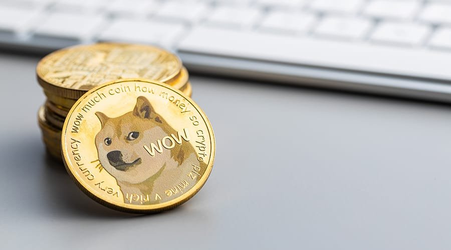 Picture of a stack of dogecoin crypto coins next to a computer keyboard. As Dogecoin gets left out of S&P Index