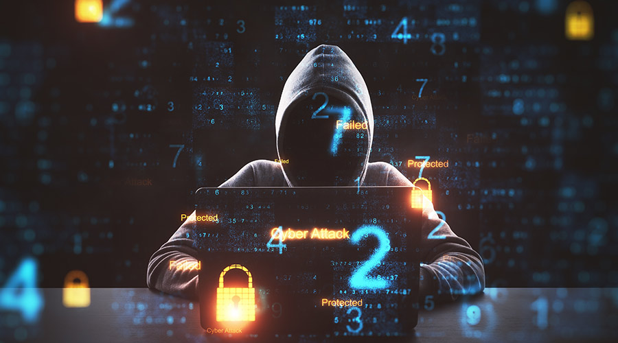 Picture of an anonymous hacker in front of a computer with computer code around them