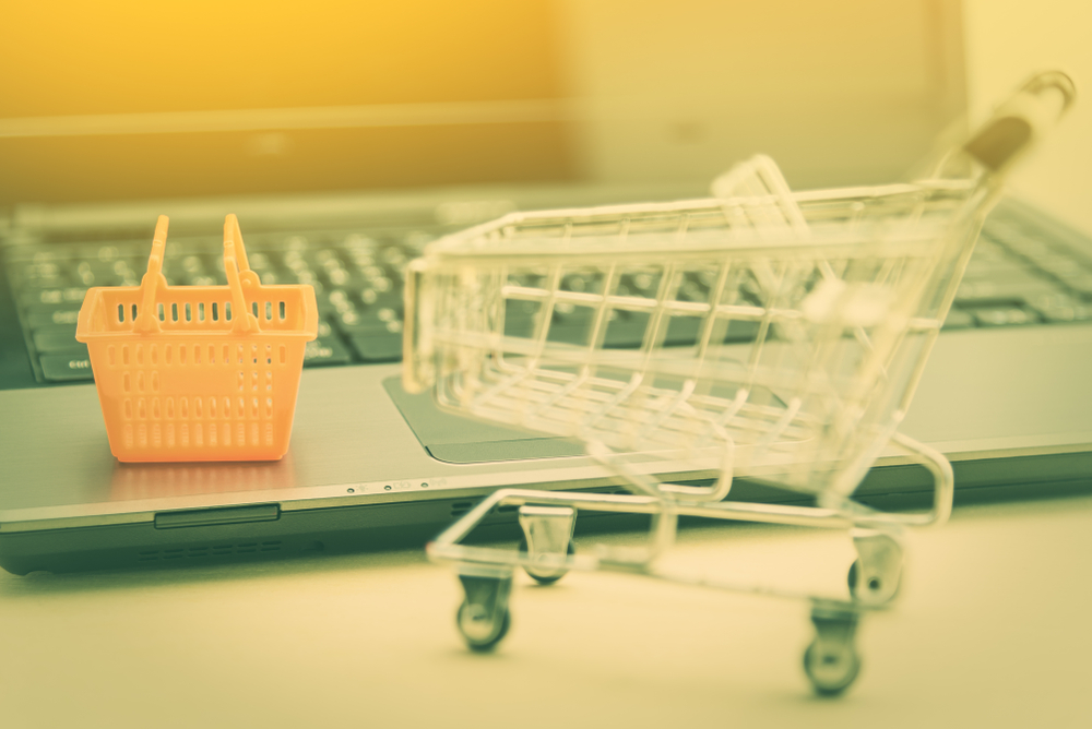 Picture of a shopping cart and basket next to a computer