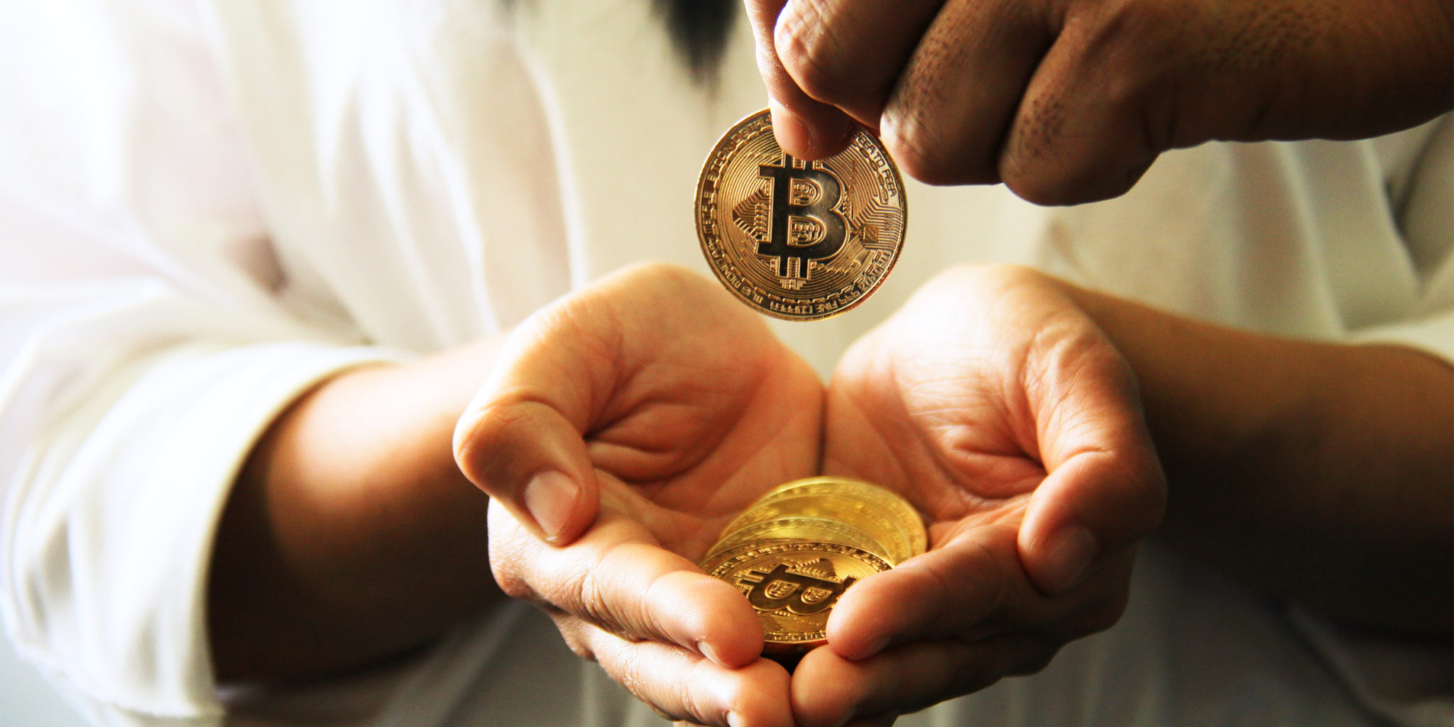 Picture of a hand holding Bitcoins, with another hand dropping a bitcoin in it