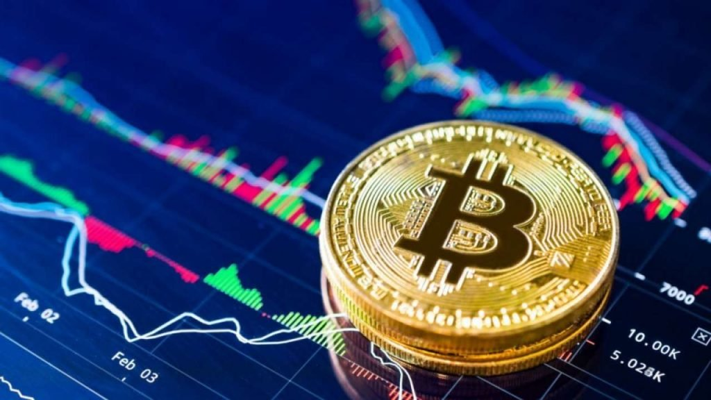 Picture of bitcoin crypto coins stacked together on top of a screen with a market chart on it