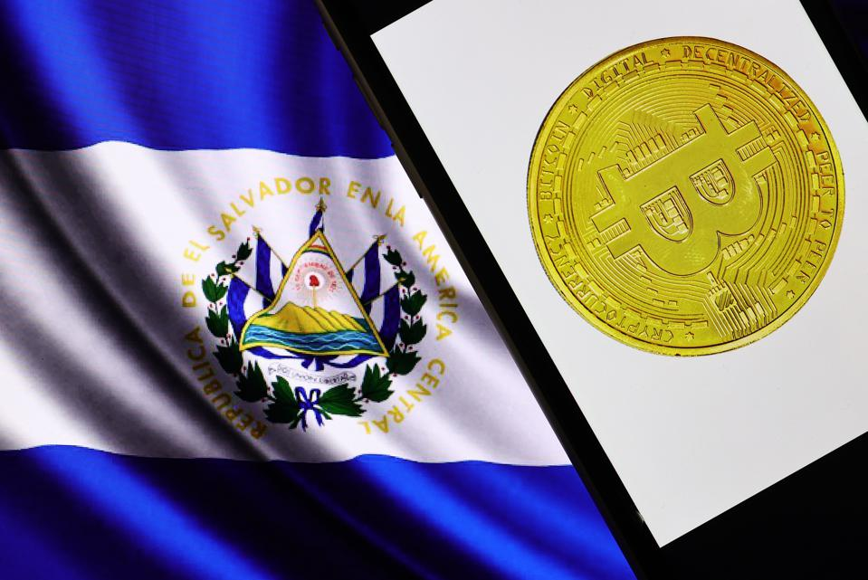 Picture of El Salvador flag with a mobile phone showing a bitcoin next to it