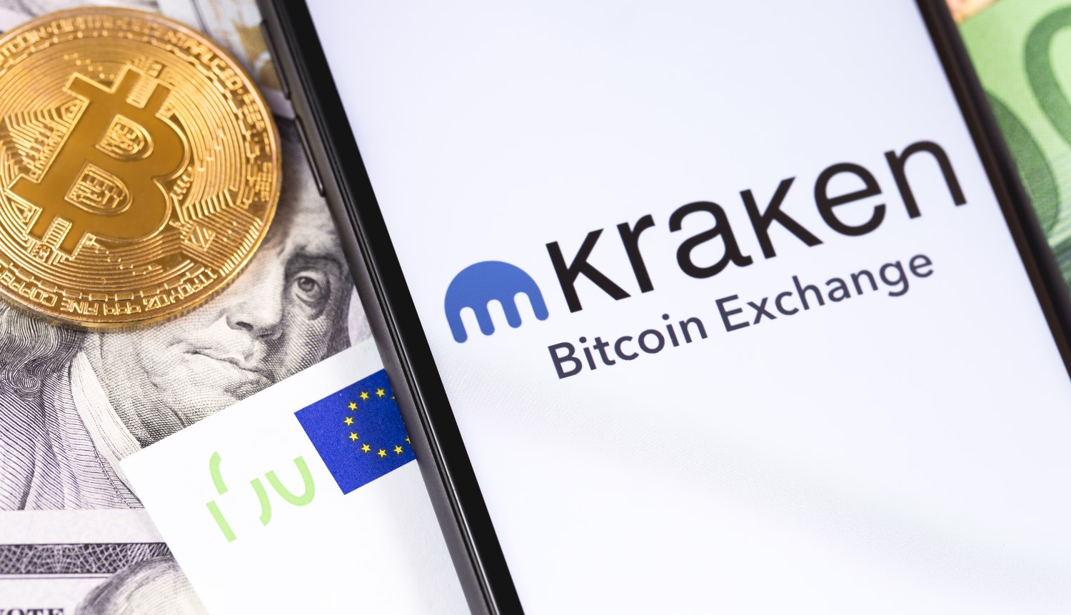 Picture of a gold bitcoin next to a smart phone with the Kraken app open on it