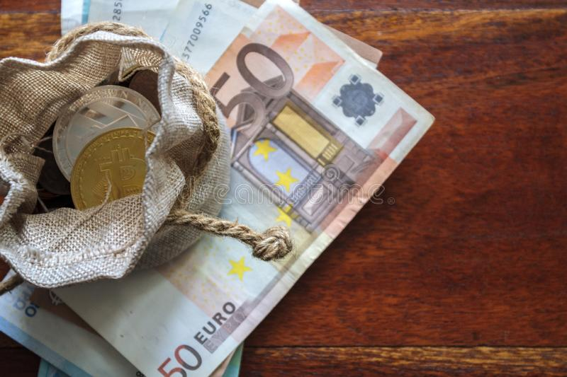 Picture of a small purse with crypto coins in it sitting on top of a stack of €50 notes, depicting MrBeast crypto holdings
