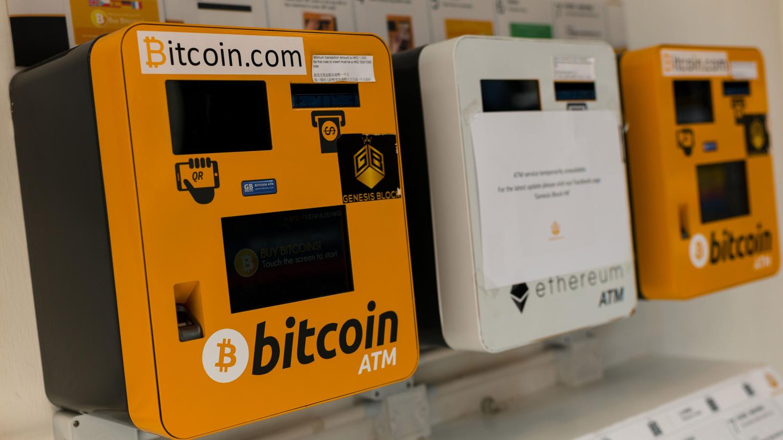 Bitcoin of three bitcoin ATMs mounted side by side on the wall