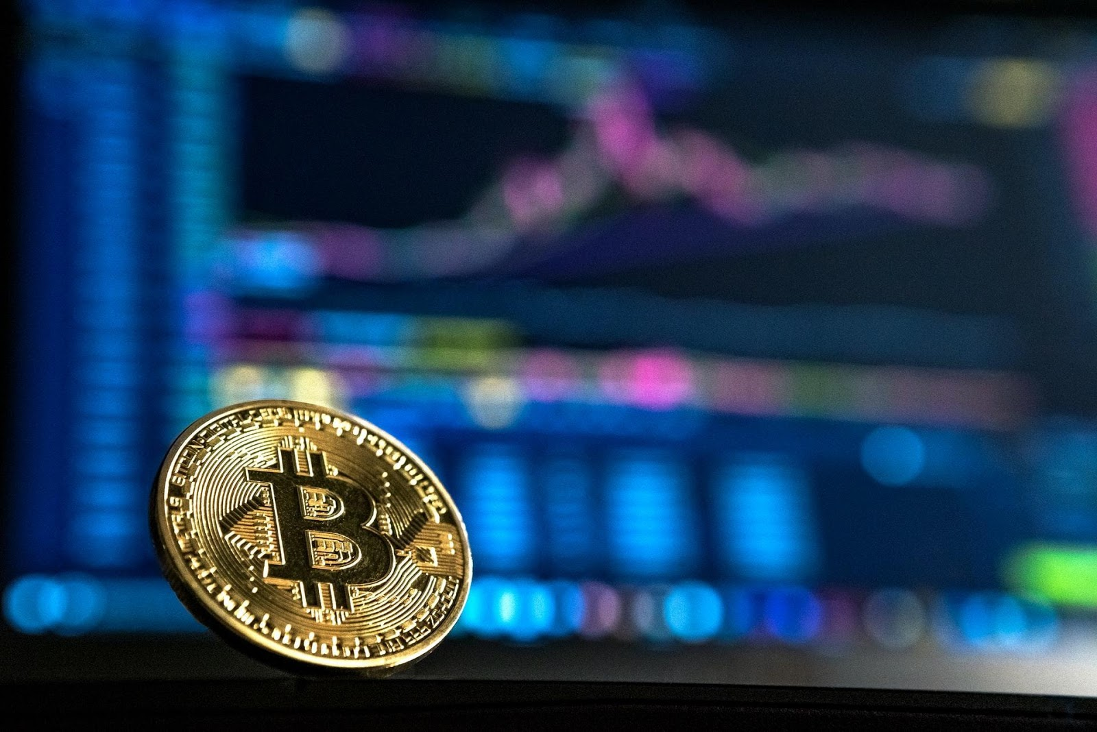 Picture of a gold bitcoin in front of a blurred market chart