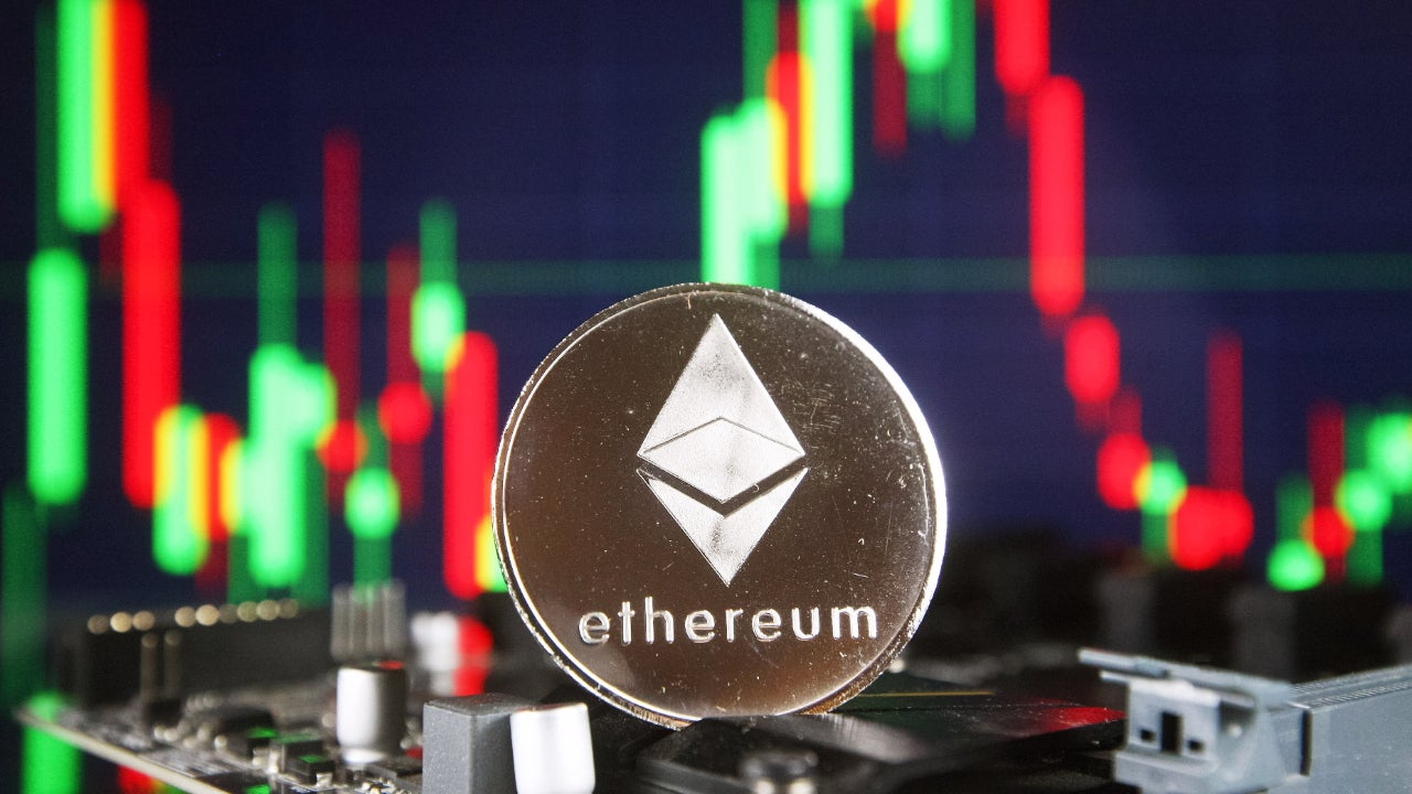 Picture of a silver ETH coin in front of a green and red candlestick chart
