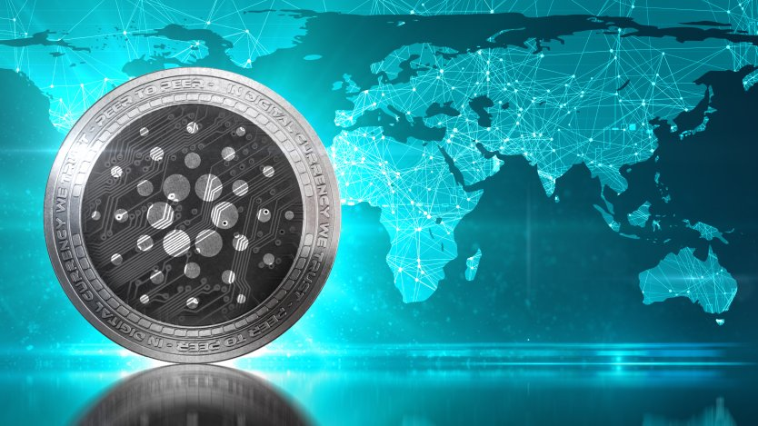 Picture of a Cardano coin in front of a map of the world